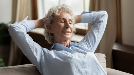 Calm 60s mature grey-haired woman in casual clothes closed eyes puts hands behind head enjoy fresh breath air in air-conditioned flat, resting alone, reduces fatigue, daydreaming feels serene at home Stock fotó