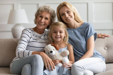 Happy family portrait, Mothers or International Womans Day holiday celebrations concept. Elderly grandmother young mother and little adorable granddaughter with plush toy sit on couch pose for camera