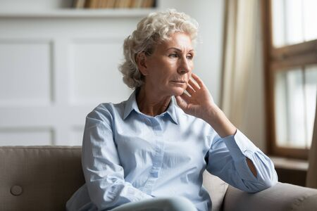 Concerned worried old woman lost in sad thoughts sit on couch in living room alone thinking about life personal or health troubles. Pensive grandmother feels melancholic, loneliness solitude concept