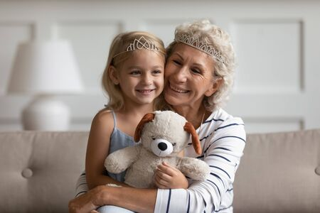 Older younger generations relatives people wear crowns on heads play sitting on couch at home. Loving elderly grandma hugs little princess kid girl hold stuffed bear toy enjoy priceless time together Reklamní fotografie