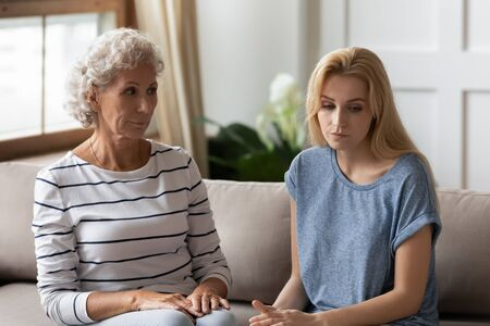 Generational gap, misunderstanding, different opinions and multi generational family conflict concept. Elderly 50s mom grown up daughter sit on couch in silence thinking feeling annoyed after dispute