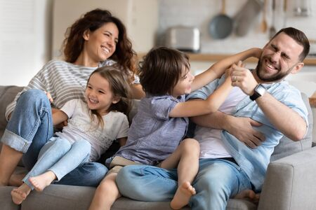 Close up happy preschool boy tickling young father near smiling mother and sister sitting on couch in living room. Family having fun at home. Parents playing with cute daughter and son Standard-Bild