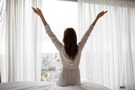 Back view of happy positive young female sit on bed stretch hands welcome new sunny day, overjoyed optimistic woman in white bathrobe wake up in bright bedroom meet good morning at home or hotel