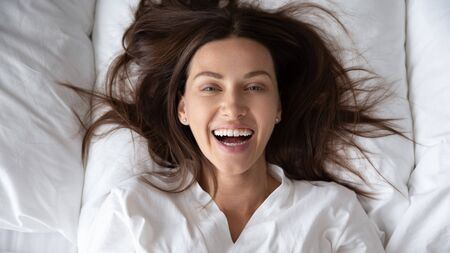 Top view portrait of happy millennial female rest wake up on fluffy pillow in white bed look at camera posing, smiling young woman awaken in cozy bedroom in the morning after good night sleep