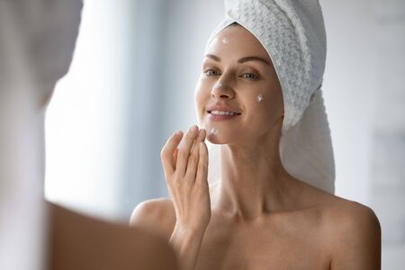 Beautiful young woman after shower look in mirror apply daily moisturizing facial cream or serum, millennial female do morning face daily treatment or beauty procedures in bathroom, skincare concept Archivio Fotografico