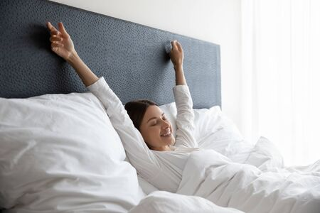 Happy young female wake up in comfortable white bed stretch welcome new sunny day, smiling woman awaken in cozy home bedroom relax rest enjoy early leisure morning or weekend