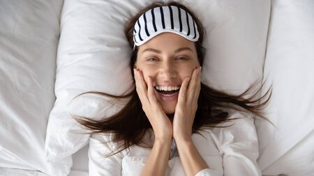 Top view portrait of smiling young woman wake up in the morning lying on fluffy soft white pillow feel optimistic, happy millennial female with sleeping mask awaken in cozy home