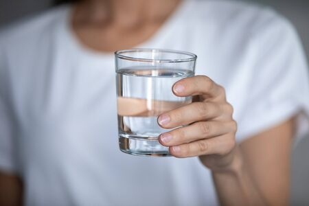 Close up of young woman hold glass with crystal clear mineral water drinking manage body balance, thirsty millennial female with clean aqua recommend follow healthy lifestyle, hydration, diet concept Stock fotó - 150294008