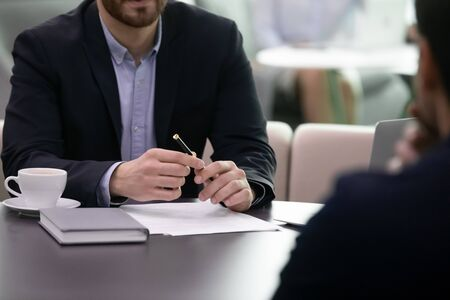 Close up of financial advisor making notes during meeting with client. Insuarence agent, realtor or lawyer consulting business man. Businessman before signing contract or making investment