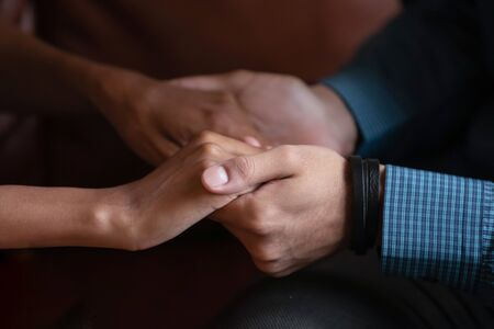 Multiethnic couple in love holding hands close up image. Mixed race woman and caucasian man having heart-to-heart talk showing protection, give psychological aid to friend, declaration of love concept
