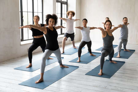 Strong sporty african american female instructor giving yoga class in modern studio, standing indoors with young happy mixed race people in warrior II second pose, enjoying working out together.