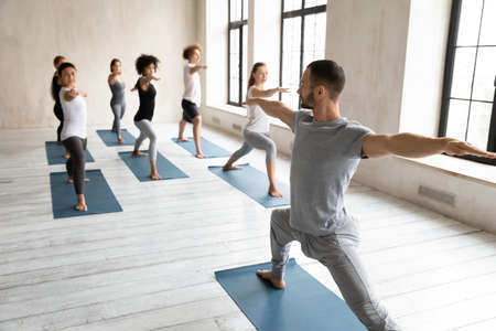 Professional male fit trainer standing in front of diverse students, giving yoga master class to multiracial young people, practicing warrior virabhadrasana second pose together in modern studio club.