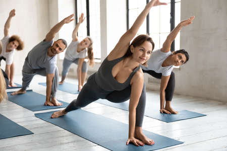 Healthy flexible young female trainer leading class to happy diverse people, practicing extended side angle position barefoot on floor mat, relieving stiffness in shoulders and back in parsvakonasana.