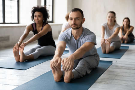 Focused professional male instructor leading yoga class in modern studio, barefoot diverse people in activewear stretching legs muscles in seated forward bend pose, enjoying morning workout class.
