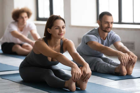 Happy young beautiful european appearance woman touching barefoot toes, stretching back and legs muscles in seated forward bend pose, practicing yoga with friends at group exercise indoors in club.
