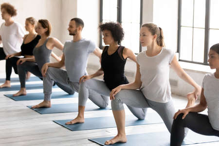 Focused young strong mixed race people in activewear practicing Eka Pada Rajakapotasana II position barefoot on floor mat, stretching body muscles in One Legged King Pigeon pose at yoga class.