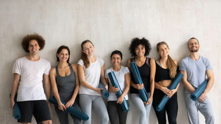Portrait of young happy multiracial friendly slim people in sportswear and rubber mats posing near wall in modern sport club, feeling good after morning yoga group workout, looking at camera.
