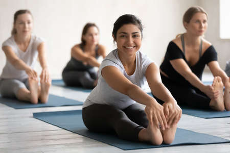 Full length happy young sporty active indian ethnicity woman sitting in seated forward bend position, looking at camera. Smiling millennial biracial female yoga beginner enjoying exercises at class.