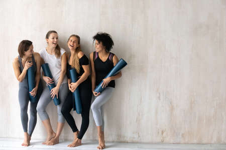 Full length emotional pretty young multiracial fit girls in activewear and floor mats in hands having fun before yoga class workout start, standing near wall with copy space for advertisement text.
