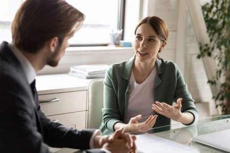 Motivated diverse Caucasian colleagues or partners talk discuss business ideas at meeting in office, confident female employee speak at interview with employer or boss, make good first impression