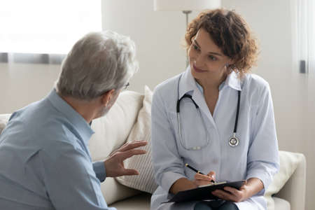 Smiling young female doctor visit mature male patient at home, do regular checkup consultation, happy woman nurse or caregiver talk consult give help to senior man client, elderly healthcare concept