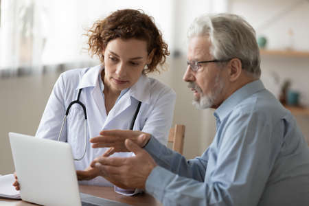 Young female doctor consult elderly male patient in hospital, discuss healthcare insurance on laptop, woman physician talk with mature man client at consultation in private clinic, geriatrics concept Banque d'images