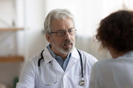 Old Caucasian male doctor in white medical uniform talk consult female patient at meeting in hospital, mature man GP or physician speak discuss illness or checkup with client at consultation in clinic