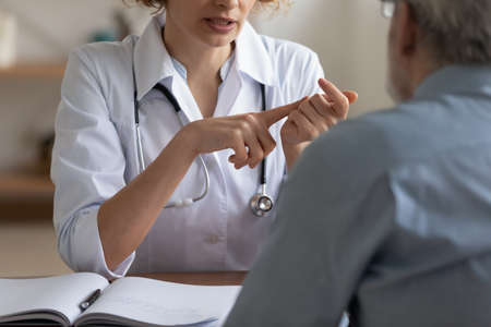 Crop close up of woman doctor talk consult mature male patient at regular checkup in hospital, female GP or nurse speak discuss anamnesis or results with senior man client at consultation in clinic