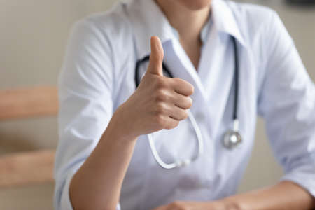 Crop close up of female doctor or GP in white medical uniform show thumb up recommend good quality medical service, woman nurse or physician give recommendation to healthcare system in hospital