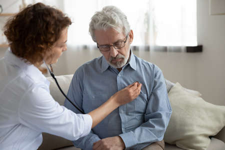 Caring female doctor hold stethoscope listen to sick mature male patient heart rate, visit pensioner at home, woman nurse or cardiologist do regular checkup for senior man client, healthcare concept