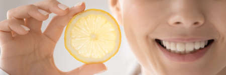 Cropped wide image close up woman with healthy beaming toothy smile holding fresh lemon slice, beautiful girl recommending organic cosmetics, beauty procedure, natural treatment, skincare routine