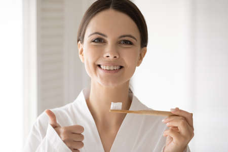 Head shot portrait satisfied young woman with healthy toothy smile holding eco toothbrush, showing thumb up, happy girl wearing white bathrobe recommending eco-friendly product for oral hygiene