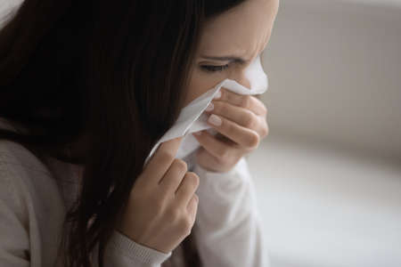 Close up sick young woman blowing nose, holding white paper tissue napkin handkerchief, unhealthy female feeling unwell, sneezing, symptom of chronic sinusitis, cold or flu, seasonal allergy concept