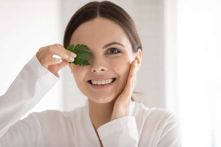 Head shot portrait smiling young woman holding green parsley leaf, happy pretty girl with healthy toothy smile and perfect smooth skin looking at camera, enjoying organic natural product