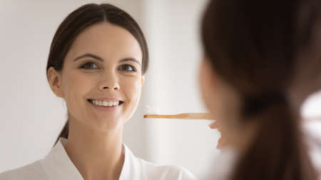 Head shot mirror reflection smiling young woman wearing bathrobe holding bamboo eco toothbrush with toothpaste, attractive girl satisfied customer choosing eco-friendly product for oral hygiene