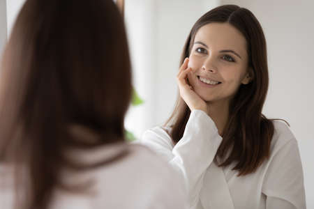 Smiling beautiful young woman looking at mirror in bathroom, attractive girl wearing white bathrobe touching perfect healthy smooth skin, enjoying morning routine, everyday skincare procedure