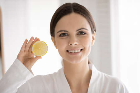 Head shot portrait woman with healthy beaming toothy smile holding slice of fresh lemon, looking at camera, beautiful girl wearing white bathrobe recommending organic cosmetics, beauty procedure