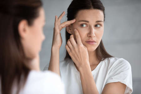 Anxious young woman look in the mirror worried about wrinkle or acne on unhealthy skin, upset unhappy millennial female examine squeeze pimple on face, cosmetology, skincare concept Reklamní fotografie