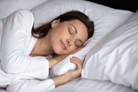 Peaceful young woman lying on fluffy pillow sleep see dreams in cozy bed at home or hotel bedroom, asleep calm millennial female relax rest in comfortable bed in the morning, relaxation concept