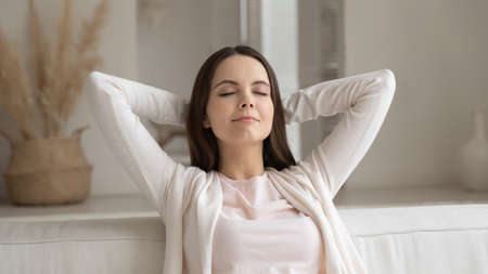 Close up calm peaceful young woman relaxing on cozy couch, sitting with closed eyes and hands behind head, leaning back, enjoying lazy weekend, breathing air, meditating, taking nap at home