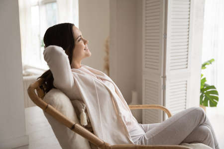 Smiling beautiful young woman relaxing, leaning back in cozy chair at home, sitting with hands behind head, looking at window, dreaming about good future, new opportunities, enjoying morning Banco de Imagens