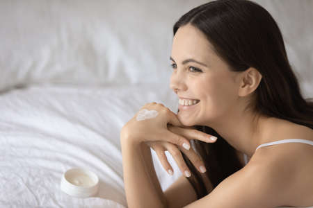 Overjoyed young woman with heart shape moisturizing cream on hand relaxing on cozy bed close up, happy attractive girl with healthy toothy smile enjoying daily skincare procedure at home 免版税图像