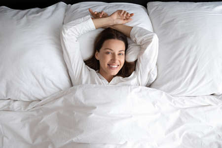 Happy young woman lying in comfortable bed on fluffy pillow under linen sheets look at camera smiling, overjoyed millennial female relax rest in cozy home or hotel bedroom wake up in the morning