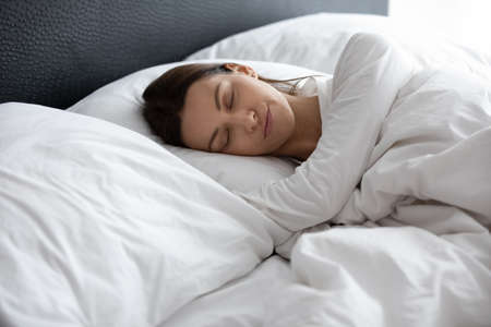 Happy young woman lying in cozy white bed under linen shades on soft fluffy pillow sleeping in morning, calm female take nap relax rest in comfortable hotel or home bedroom, relaxation concept