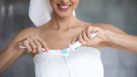 Close up of smiling young woman in towel after shower apply whitening toothpaste on toothbrush, millennial female do perform daily morning oral hygiene routine in bathroom, dental care concept