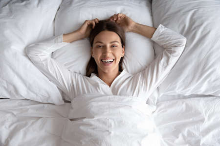 Top view portrait of smiling millennial woman lying relaxing on comfortable white bed on fluffy pillow, happy young female rest wake up in the morning after good sleep in cozy home or hotel bedroom Reklamní fotografie