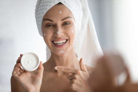 Portrait of smiling young woman look in mirror in bathroom apply facial cream recommend beauty product, happy lady use moisturizing mask or balm on face do skincare procedures at home