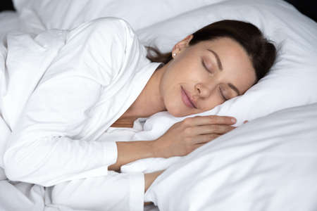 Happy young woman in bathrobe or pajama sleep peacefully on soft fluffy pillow in cozy home or hotel bedroom, calm millennial female relax rest take nap in comfortable bed see dreams in the morning