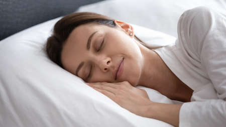 Calm millennial female sleep peacefully on soft fluffy white pillow see dreams lying in cozy bedroom, peaceful young woman relax rest take nap in comfortable bed at home or hotel, relaxation concept