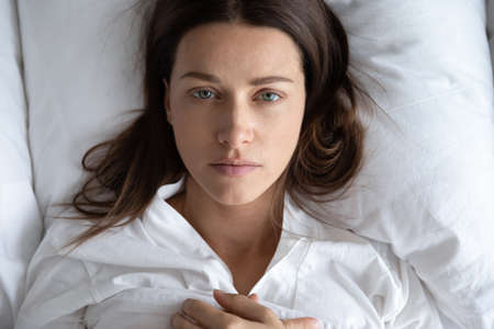 Top view of depressed upset young woman lie relax on white pillow linen sheets feel distressed lonely, sad millennial female rest in home bedroom suffer from depression or insomnia, having problems Reklamní fotografie